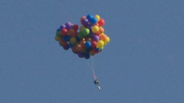 Hombre sobrevuela ciudad atado a una silla con 100 globos de helio
